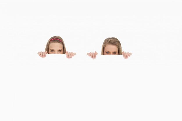 Close-up de mulheres jovens escondidas atrás de um sinal em branco
