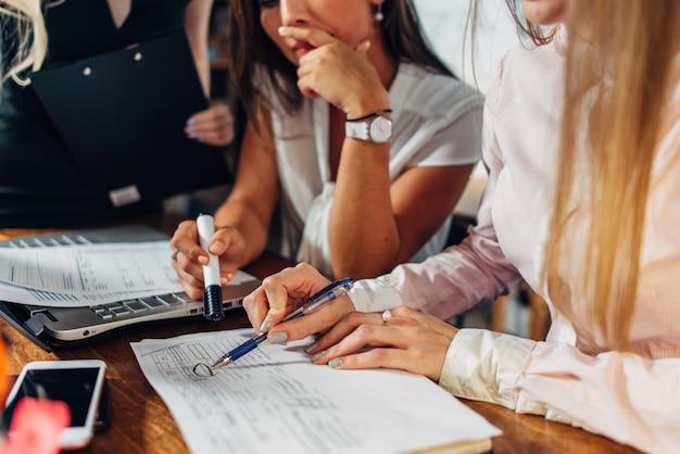 Close-up de mulheres jovens que trabalham na papelada de contabilidade, verificando e apontando para documentos.
