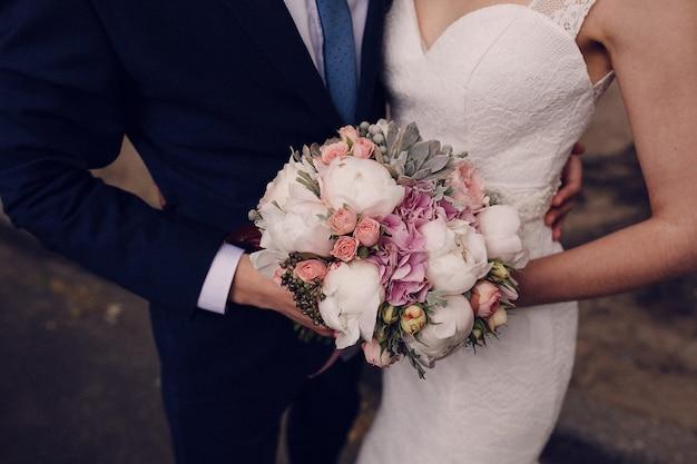 Close-up de noivos segurando o buquê de casamento
