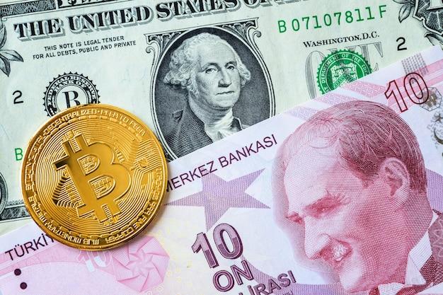 Close-up de notas de dez liras turcas e de um dólar americano e uma moeda bitcoin dourada