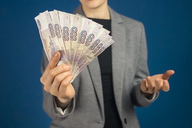 Close-up de notas de rublo russo na mão de uma mulher com uma jaqueta cinza. foco seletivo.