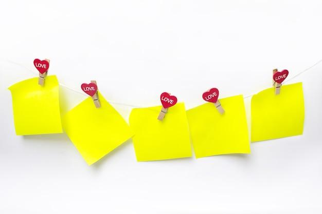 Close-up de notas em branco amarelas pendurado varal com corações contra uma parede branca.