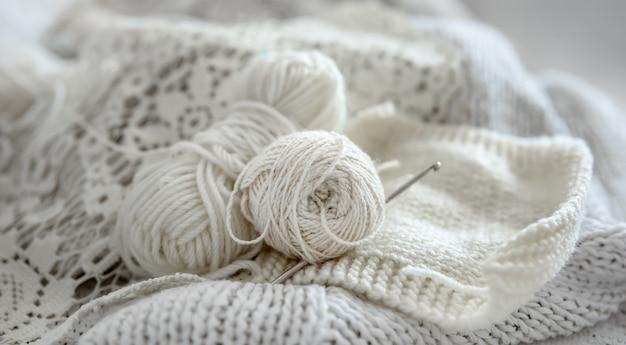 Close-up de novelos de lã para tricô em tons pastel.
