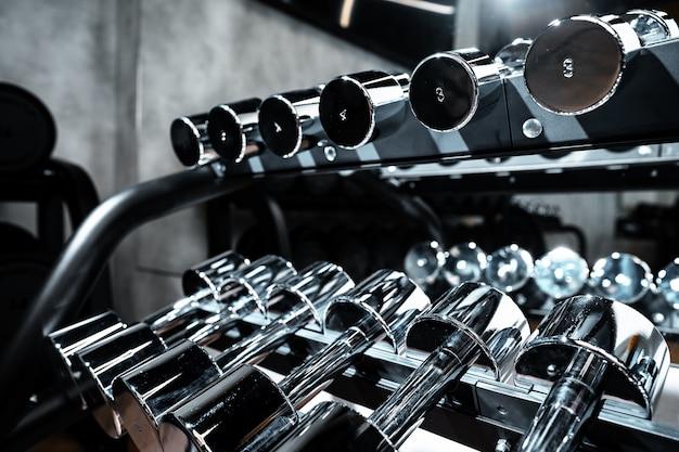 Close-up de novos halteres em um rack em uma academia