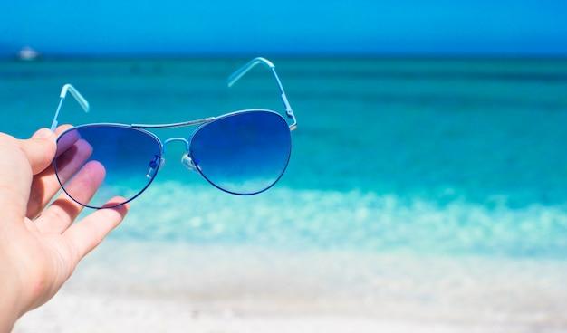 Close-up de óculos coloridos azuis na praia tropical