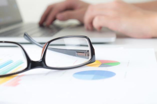 Close-up de óculos de negócios na mesa com gráficos e laptops no trabalho