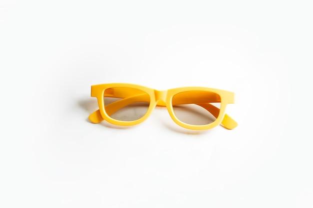 Close-up de óculos de plástico amarelos para os olhos, isolados na superfície branca com sombras.