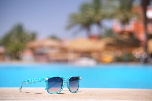 Close-up de óculos de sol azuis ao lado da piscina no resort tropical em dia de sol quente. conceito de férias de verão.