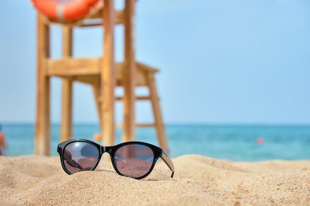 Close-up de óculos de sol protetores pretos na praia de areia à beira-mar tropical em dia de sol quente. conceito de férias de verão.