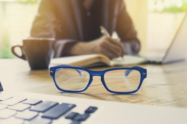 Close-up de óculos e homem de negócios trabalhando e escrevendo no notenook com o computador laptop em backfround borrado. foco seletivo.