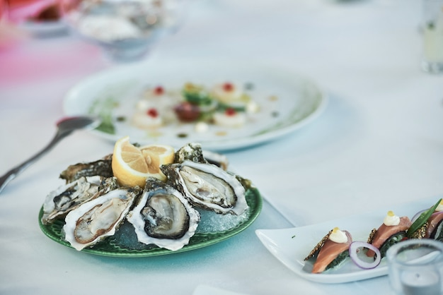 Close-up de ostras frescas com limão na mesa do restaurante.