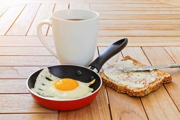 Close-up de ovo frito na panela, torradas e caneca de café na mesa de madeira