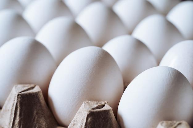 Close up de ovos brancos de galinha. produtos agrícolas e ovos naturais em uma bandeja de papelão.