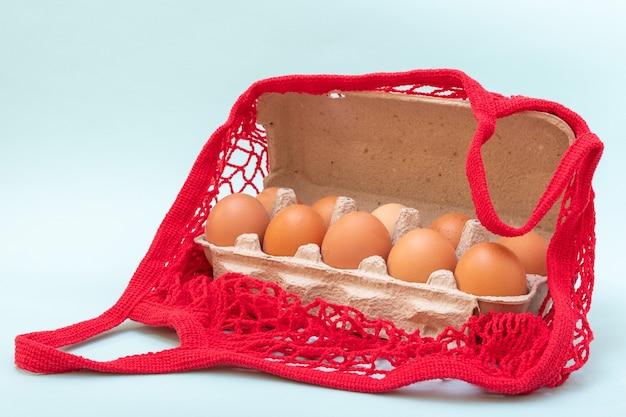 Close-up de ovos crus naturais em uma caixa de papelão para ovos e em um saco de barbante vermelho, copie o espaço. comprar ovos para o conceito de páscoa. conceito de comida saudável