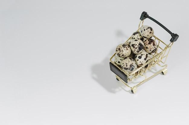 Close-up de ovos de codorna em um carrinho. sobre um fundo claro. páscoa e conceito de venda de ovos.
