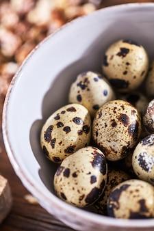 Close up de ovos de codorna orgânicos em um prato branco sobre uma mesa de madeira