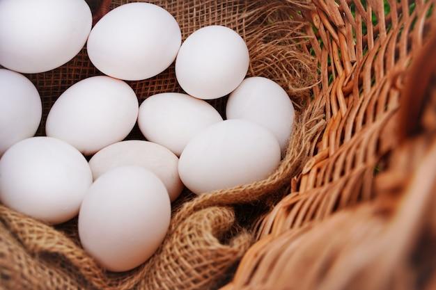 Close up de ovos de galinha branca rústica orgânica em cama de serapilheira natural em uma cesta ...