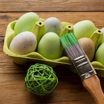 Close-up de ovos de páscoa coloridos em caixa com pincel e decoração
