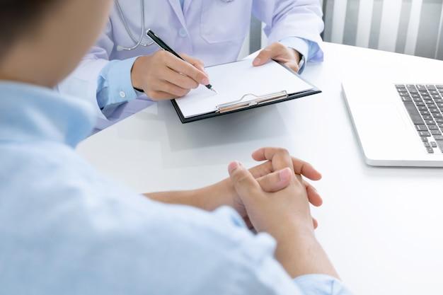 Close up de paciente e médico tomando notas em um hospital ou clínica
