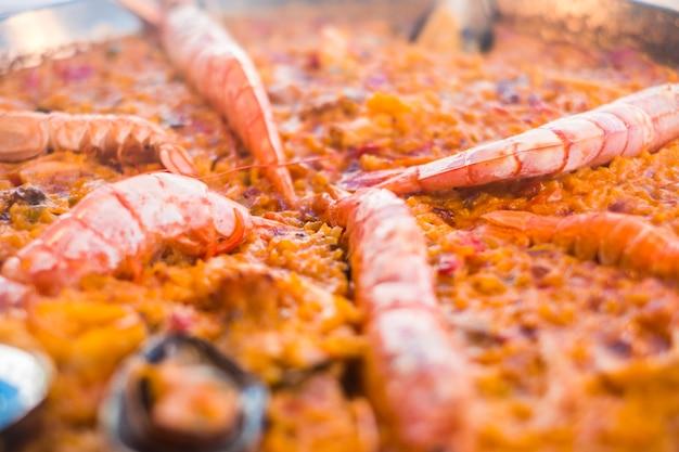 Close up de paella deliciosa comida tradicional da espanha com arroz de carne e peixes como camarões
