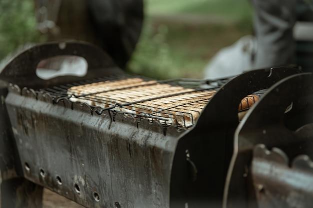 Close-up de pães de cachorro-quente frito em uma grade na grelha.