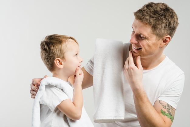 Close-up, de, pai filho, tocando, seu, queixo, com, mãos, olhando um ao outro, contra, branca, fundo