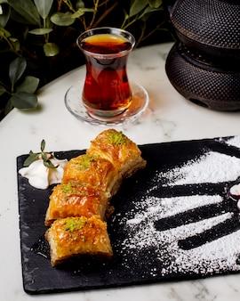Close-up de pakhlava turco com pistache servido com chá preto