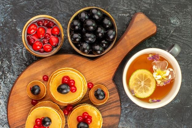 Close up de panquecas abafadas servidas com frutas e uma xícara de chá com limão