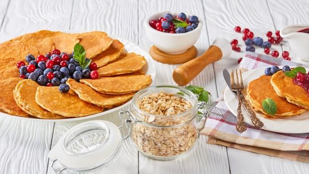 Close-up de panquecas de aveia servidas com mirtilos frescos e cranberries em um prato branco com ingredientes, garfo dourado e faca