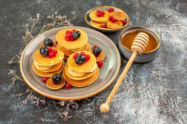 Close-up de panquecas de frutas em um prato pequeno e grande com mel