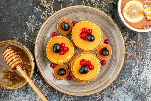 Close up de panquecas de frutas mel com uma colher de pau e uma xícara de chá