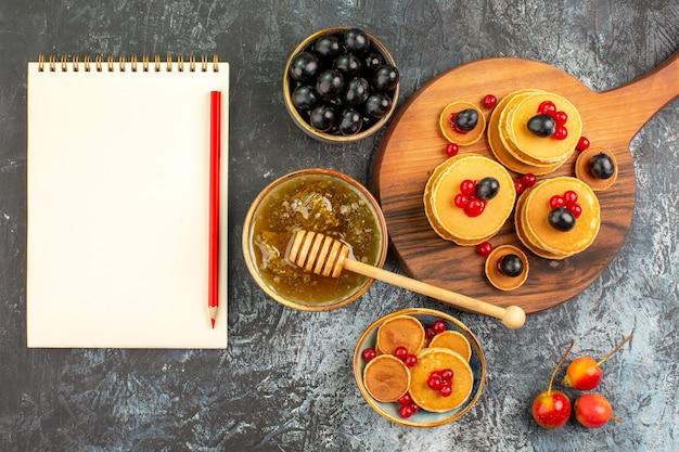 Close up de panquecas de leitelho com frutas mel, frutas e caderno