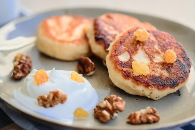 Close-up de panquecas de queijo caseiro syrniki com creme de leite e xícara de chá