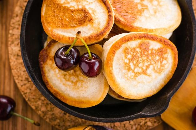 Close-up de panquecas fritas em uma panela de ferro e cerejas maduras
