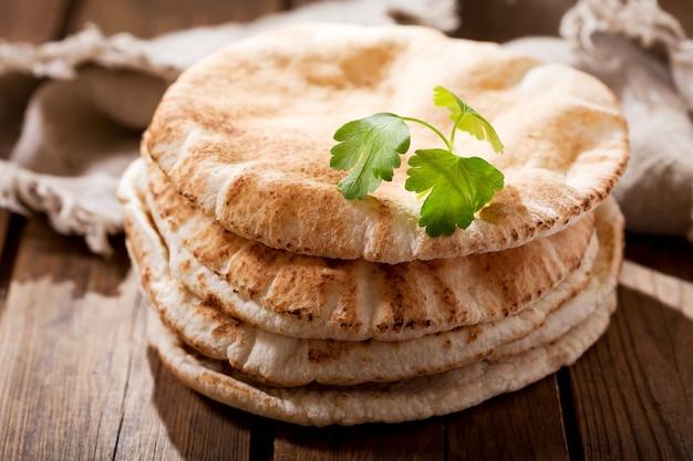 Close up de pão sírio na placa de madeira