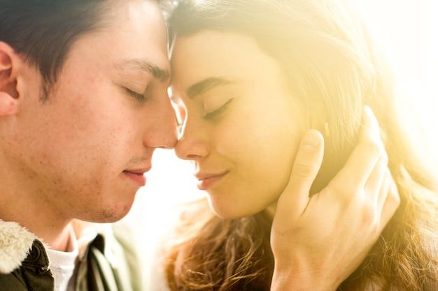 Close-up, de, par jovem, ficar, cara enfrentar, com, olhos fechados