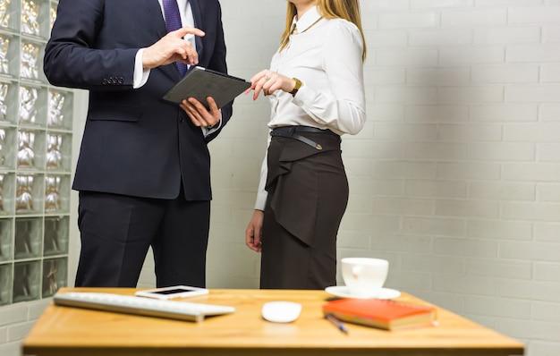 Close-up de parceiros de negócios, olhando para o documento no touchpad