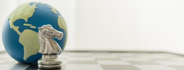 Close up de partes de xadrez de prata do cavaleiro com a mini bola do mundo no tabuleiro de xadrez com espaço da cópia.