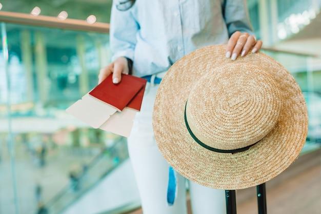 Close-up de passaportes e cartão de embarque em mãos femininas no aeroporto