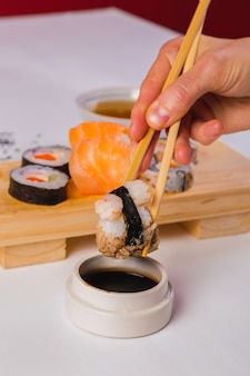 Close-up de pauzinhos pegando uma porção de sushi roll e molho de soja.