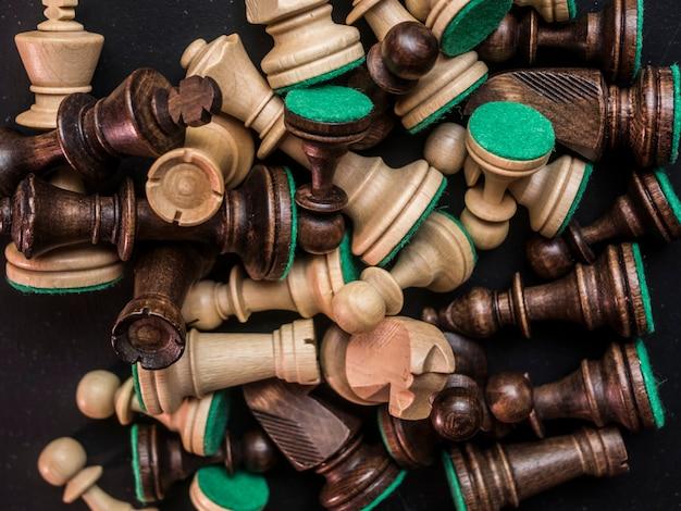 Close-up de peças de xadrez bagunçado na mesa preta escura close-up