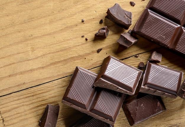 Close up de pedaços de chocolate na velha mesa de madeira