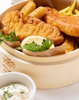 Close-up de peixe e batatas fritas em uma tigela com limão