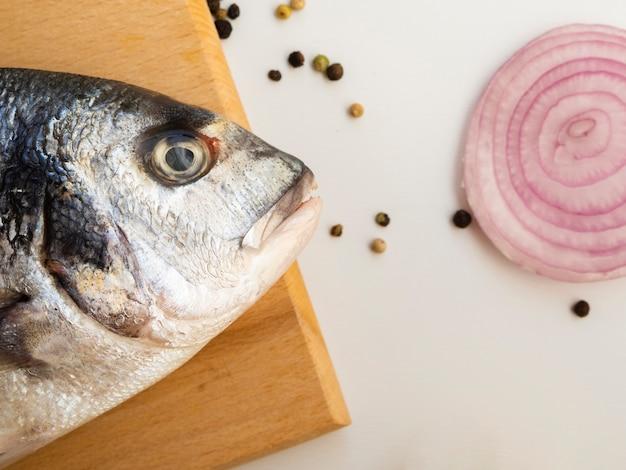 Close-up de peixe fresco ao lado de uma cebola