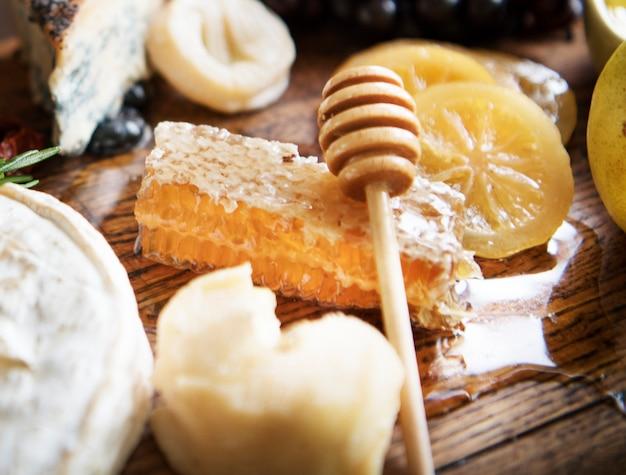Close-up de pente de mel em uma tábua de queijos