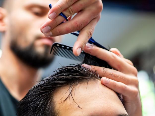 Close-up de pente nas mãos com cabeleireiro turva