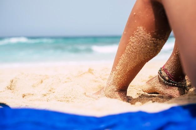 Close-up de pernas de mulher bonita na praia fazendo um banho de sol relaxante na areia e olhando para as ondas azuis do oceano. lindas pulseiras nos pés e ondas de água limpa e cristalina