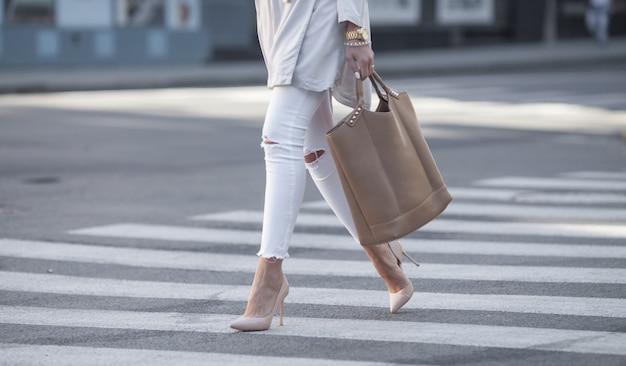 Close-up de pernas de mulher caminhando na faixa de pedestres. a mulher está usando sapatos de salto alto.