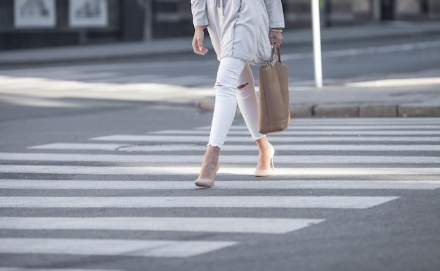 Close-up de pernas de mulher caminhando na faixa de pedestres.