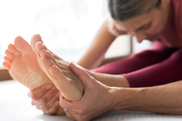 Close-up de pernas e mãos em uma vista lateral de uma mulher fitness